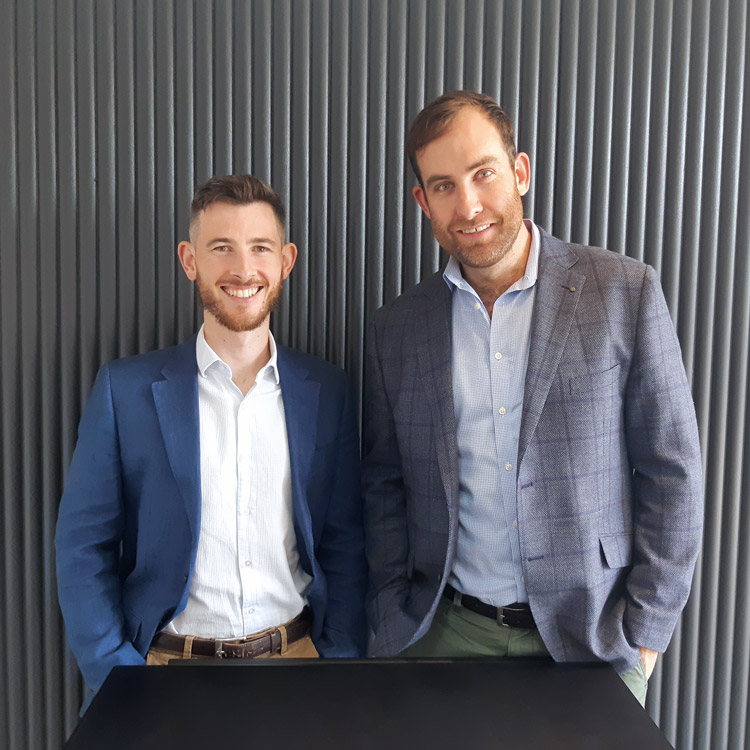Tom De Garis and Patrick Murphy standing together behind a black table in front of corrugated iron